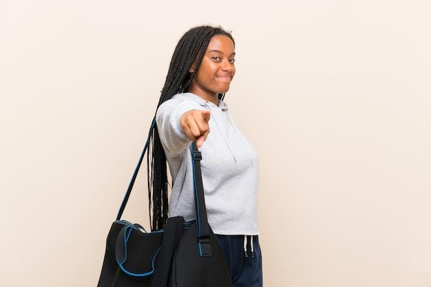 Het afrikaanse amerikaanse meisje van de sporttiener met lang gevlecht haar richt vinger op u met een zekere uitdrukking