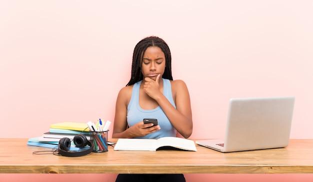 Het afrikaanse amerikaanse meisje van de tienerstudent met lang gevlecht haar in haar werkplaats die en een bericht denkt verzendt