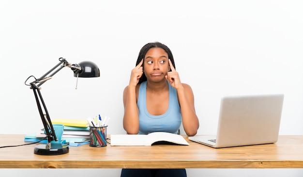 Het afrikaanse amerikaanse meisje van de tienerstudent met lang gevlecht haar in haar werkplaats die twijfels en het denken hebben