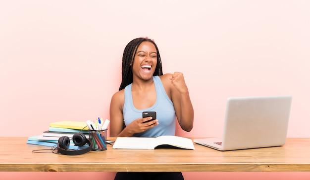 Het afrikaanse amerikaanse meisje van de tienerstudent met lang gevlecht haar in haar werkplaats met telefoon in overwinningspositie