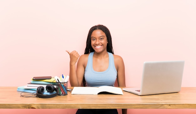 Het afrikaanse amerikaanse meisje van de tienerstudent met lang gevlecht haar op haar werkplaats die aan de kant richten om een product te presenteren