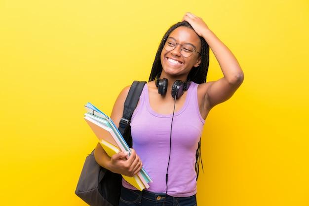 Het afrikaanse amerikaanse meisje van de tienerstudent met lang gevlecht haar over het geïsoleerde gele muur lachen