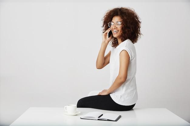 Het afrikaanse onderneemster lachen die op telefoon op het werk spreekt.