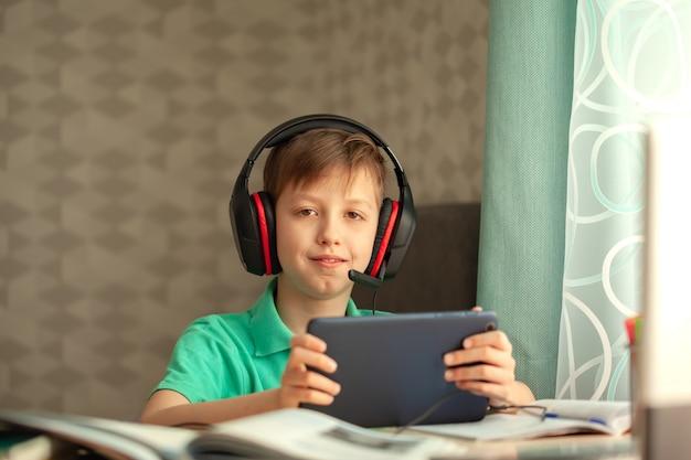 Het afstandsonderwijskind in hoofdtelefoons let op een les op een tablet. concept online onderwijs.