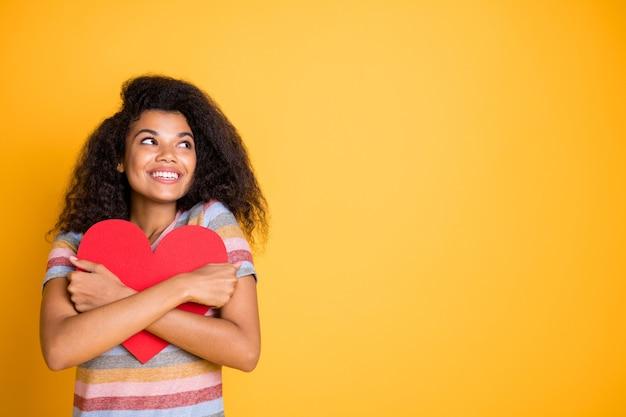 Het amerikaanse meisje van afro in gestreept t-shirt omhelst de rode kaart van het valentijnskaarthart