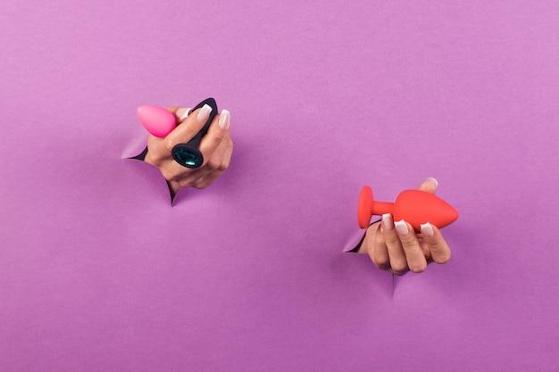 Het anale seksspeeltje op een roze achtergrond in de handen van een vrouw