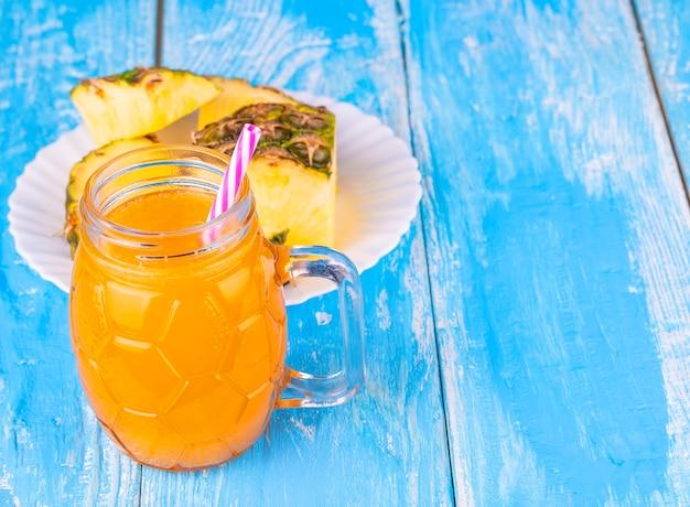 Het ananas en ananassap op het blauwe bord