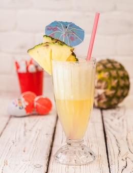 Het ananassap van het zijaanzicht met sapstro en ananasplakken en cocktailparaplu in glaskop op houten lijst