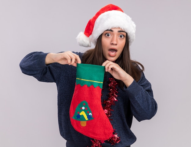 Het angstige jonge kaukasische meisje met santahoed en slinger om hals houdt kerstmiskous