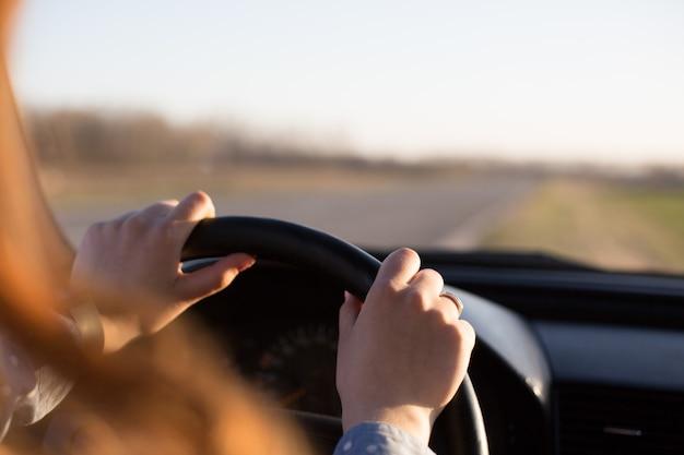 Het anonieme schot van de handen van de jonge vrouw op het stuur tijdens het besturen van de auto, het vrouwtje stopt haar voertuig aan de kant van de weg en geniet van de zonsondergang in haar auto, terwijl ze rust heeft terwijl ze alleen reist.