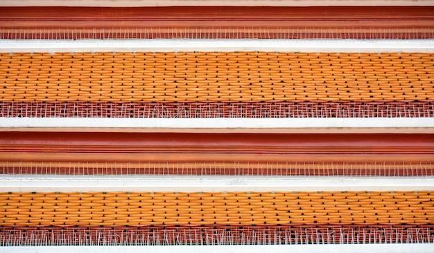 Het antieke rode en gele patroon van het tegeldak bij de tempel van boedha in thailand