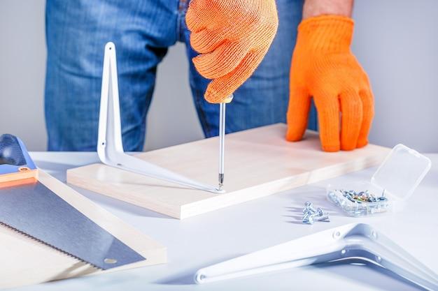 Het assembleren van de mens meubilair die schroevedraaier gebruiken. doe-het-zelf-concept.