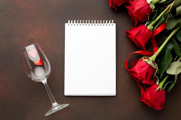 Het assortiment van de valentijnskaartendag met rozen en lege blocnote