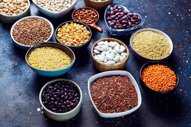 Het assortiment van peulvruchten en bonen in verschillende kommen op lichte steenachtergrond. bovenaanzicht. gezond veganistisch eiwitrijk voedsel.