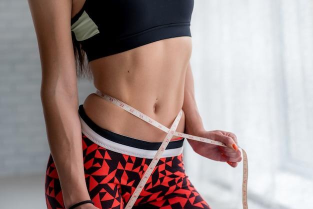 Het atletische jonge meisje meet haar slanke taille. gezonde levensstijl