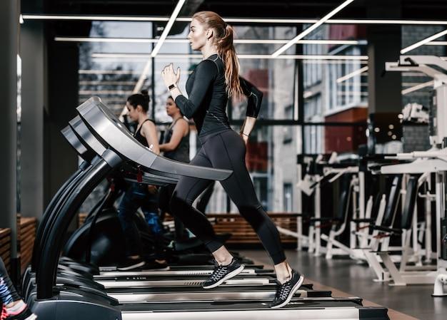Het atletische meisje gekleed in een zwarte sportkleding draait op de loopband in de moderne sportschool.