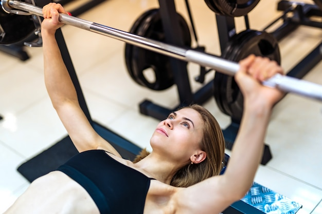 Het atletische meisje heft barbell op liggend op de bank op de simulator in de gymnastiek.
