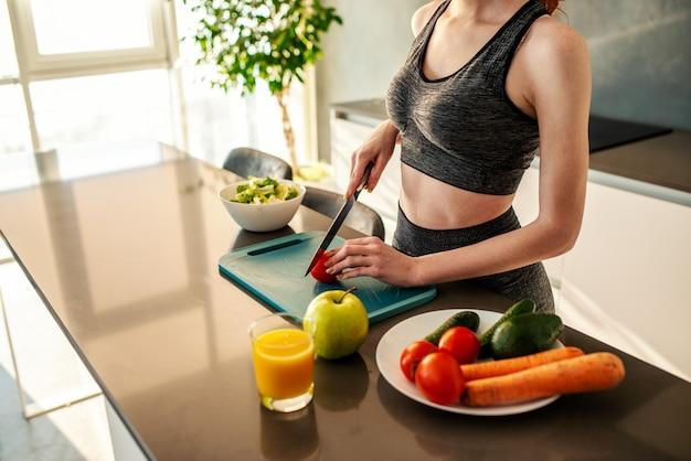 Het atletische meisje met gymnastiekkleren eet een salade in de keuken