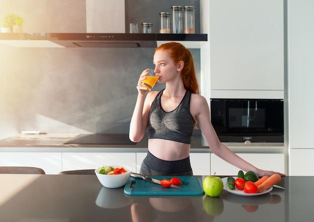 Het atletische meisje met gymnastiekkleren eet fruit in de keuken
