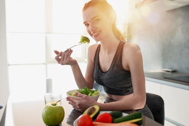 Het atletische meisje met gymnastiekkleren eet salade in de keuken