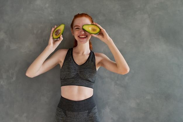 Het atletische meisje met gymnastiekkleren eet thuis avocado