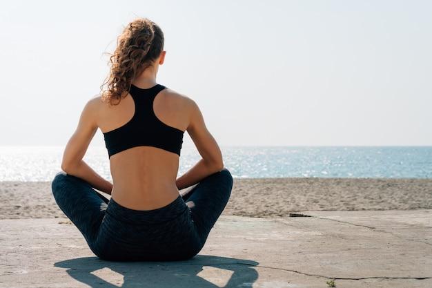 Het atletische meisje met krullend haar in een zitting van de sportenbustehouder op een strand en kijkt op zee in de ochtend