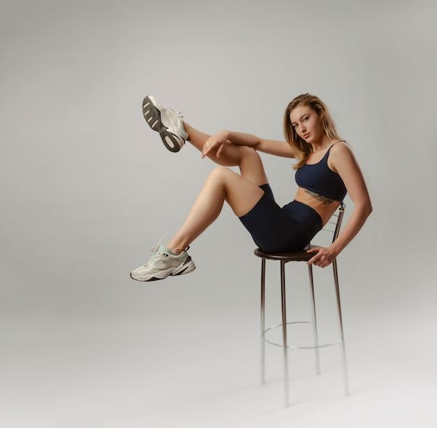 Het atletische meisje poseren in de studio op een witte achtergrond