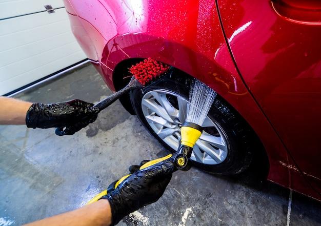 Het autowiel schoonmaken met een borstel en water.