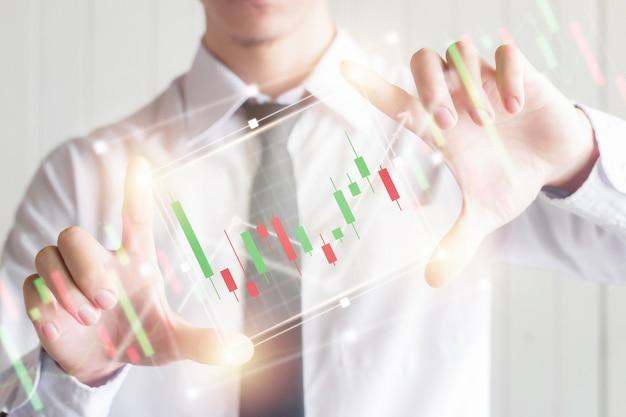 Het aziatische bedrijfs mannelijke gebruikende vinger breidt het digitale virtuele scherm met kandelaargrafiek, financieel en investeringsconcept uit
