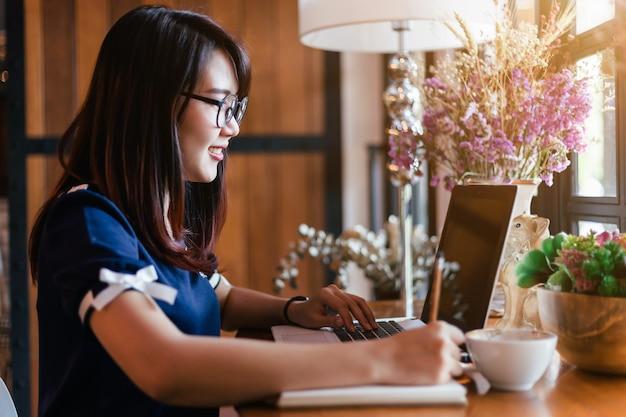 Het aziatische bedrijfsvrouw dat met laptop werkt maakt een nota in koffiewinkel zoals de achtergrond.