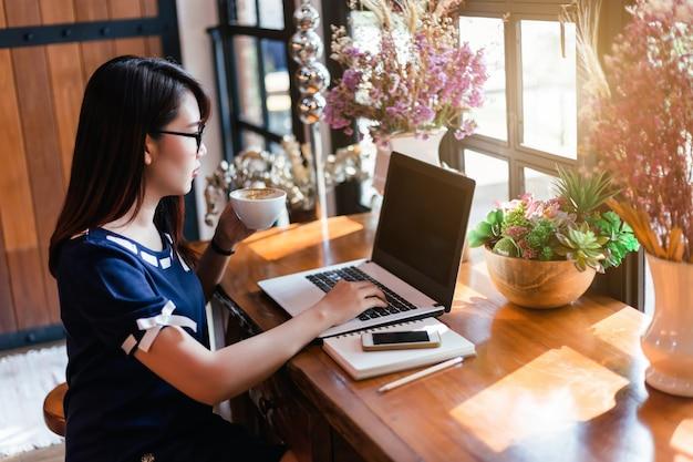 Het aziatische bedrijfsvrouw houdt een koffiemok werkend met laptop in koffiewinkel zoals de achtergrond.