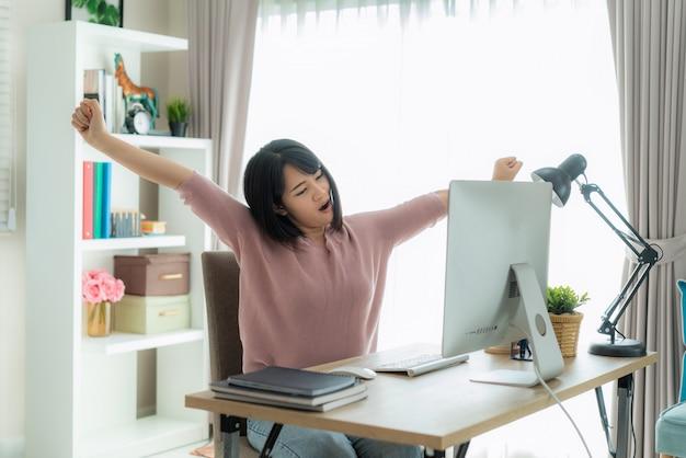 Het aziatische bedrijfsvrouwenwerk van huis en het uitrekken van haar lichaam omdat voel me vermoeid en slaperig na het werken aan computer, slim wijfje die thuis werken.