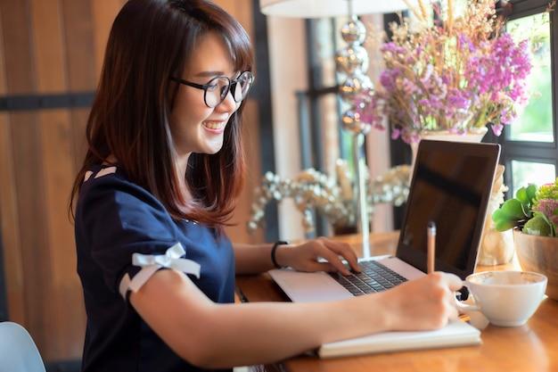 Het aziatische bedrijfswijfje dat werkt met maakt een nota met een notitieboekje en laptop