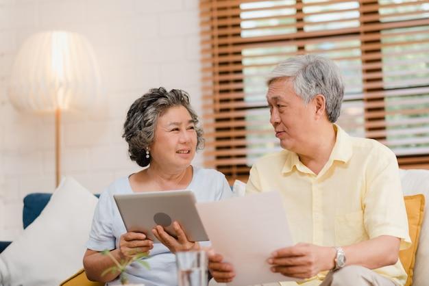 Het aziatische bejaarde paar die tablet gebruiken die op tv in woonkamer thuis letten, het paar geniet liefde van ogenblik terwijl het liggen op bank wanneer ontspannen thuis.
