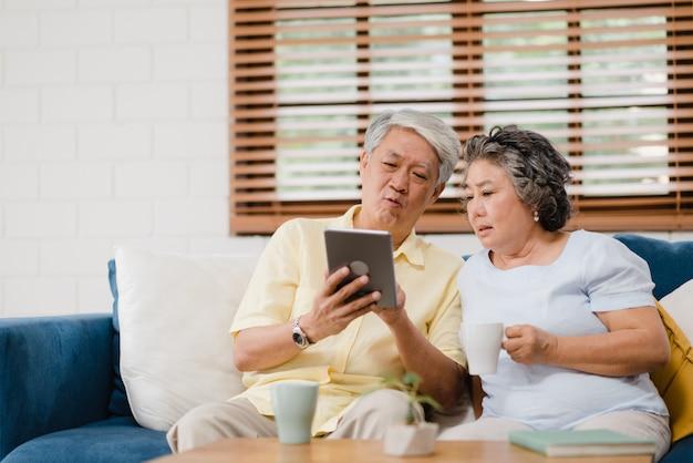 Het aziatische bejaarde paar gebruikend tablet en het drinken de koffie in woonkamer thuis, paar genieten liefde van ogenblik terwijl het liggen op bank wanneer ontspannen thuis.