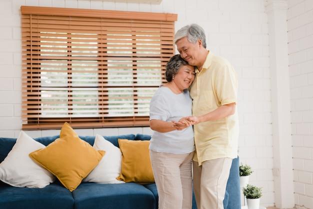 Het aziatische bejaarde paar samen dansen terwijl thuis aan muziek in woonkamer luister, het zoete paar geniet liefde van ogenblik terwijl het hebben van pret wanneer thuis ontspannen.
