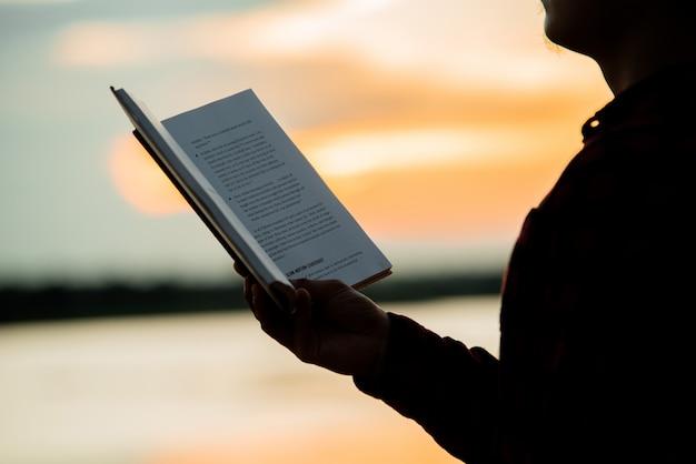 Het aziatische boek van de mensenlezing tijdens een zonsondergang