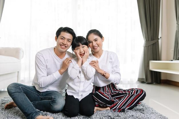 Het aziatische familieportret met het gelukkige mensen glimlachen bekijkt camera in mijn huis.