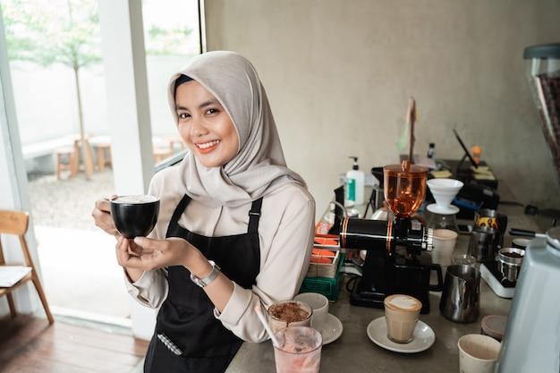 Het aziatische gesluierde serveerster glimlachen houdt een kop van koffie