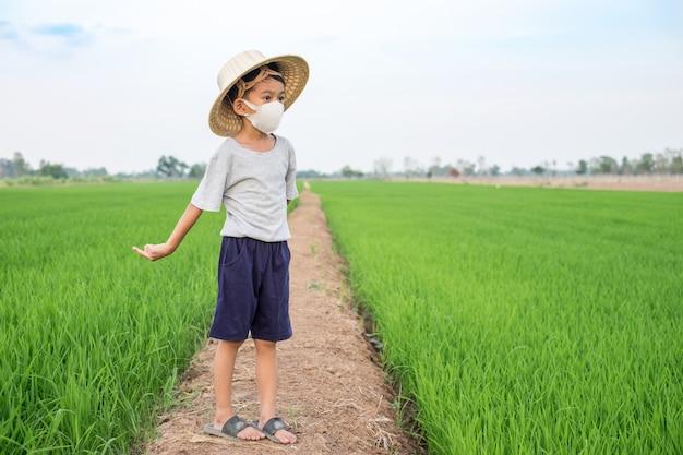 Het aziatische gezichtsmasker van de jongensslijtage en bamboehoed die zich bij rijstlandbouwbedrijf bevinden. gezond concept