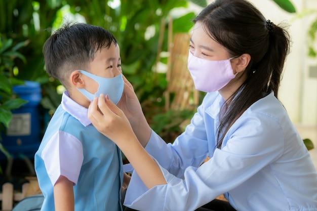 Het aziatische gezichtsmasker van het moedergebruik beschermt haar zoon alvorens naar de kleuterschool te gaan, dit beeld kan voor covid19, bescherming, familie, onderwijs en coronavirusconcept gebruiken.