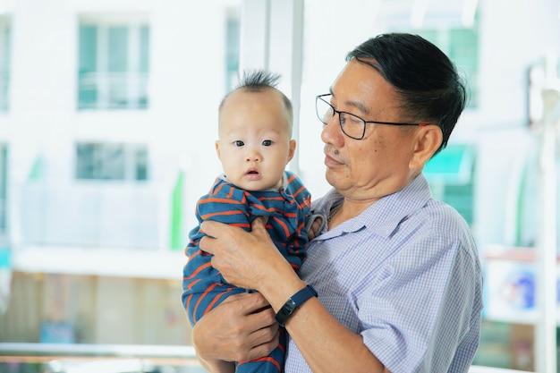 Het aziatische grootvader dragen treft voorbereidingen om een arts te zien