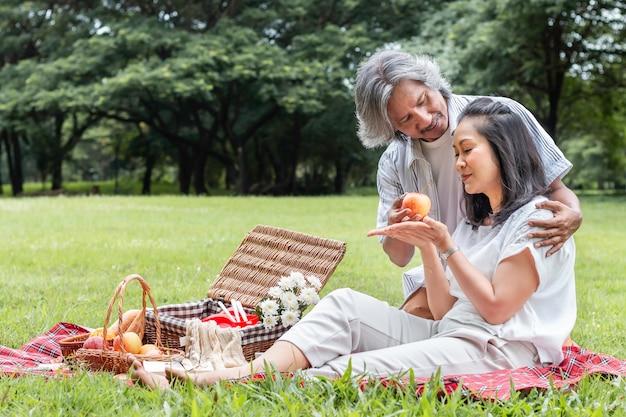 Het aziatische hogere paar ontspannen en picknick bij park. de vrouw geeft appel aan mijn echtgenoot.