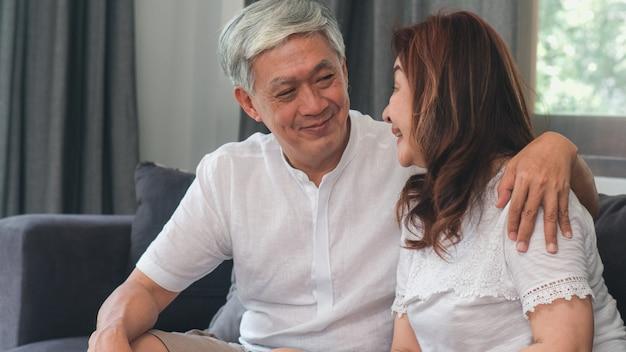 Het aziatische hogere paar ontspant thuis. aziatische hogere chinese grootouders, echtgenoot en vrouwen gelukkige glimlachomhelzing die samen terwijl thuis het liggen op bank in woonkamerconcept spreken.