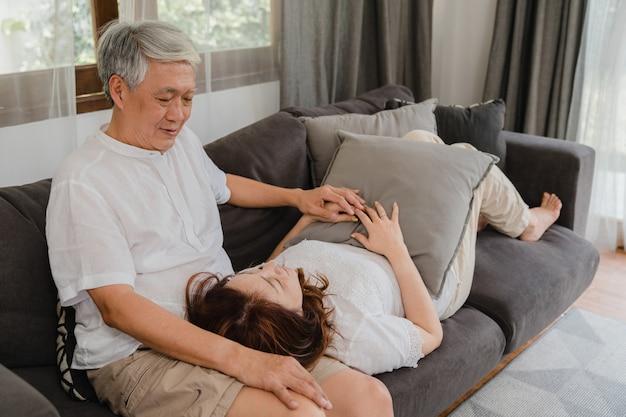 Het aziatische hogere paar ontspant thuis. de aziatische hogere chinese grootouders, omhelzing van de echtgenoot liggen de gelukkige glimlach haar vrouwenoverlapping terwijl thuis het liggen op bank in woonkamerconcept.