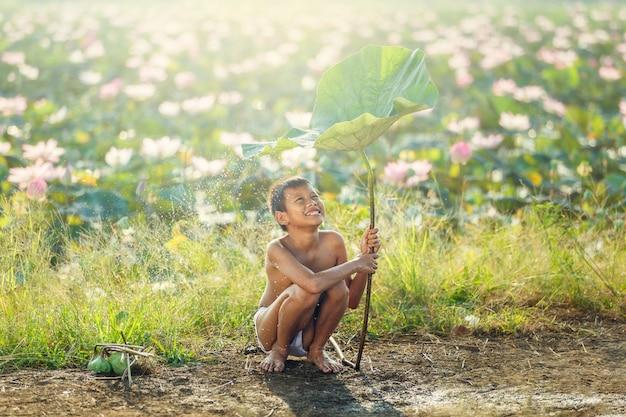 Het aziatische jong geitje glimlachen en geluk speelwater onder lotusbloemblad na het regenen van dag bij platteland in thailand.
