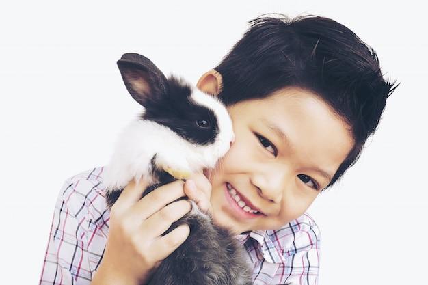 Het aziatische jong geitje spelen met mooi babykonijn dat over wit wordt geïsoleerd
