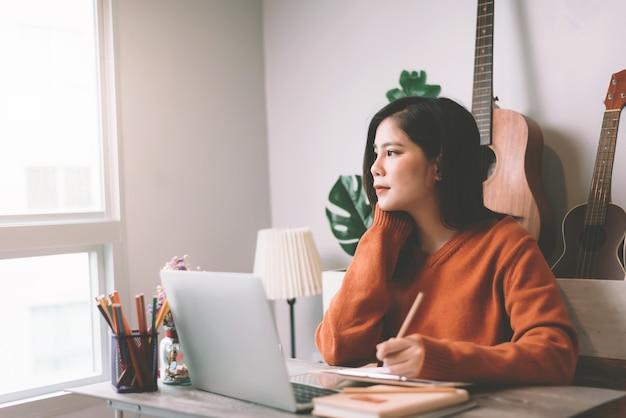 Het aziatische jonge creatieve vrouw werken aan laptop computer in de ochtend die - van huisconcept werken