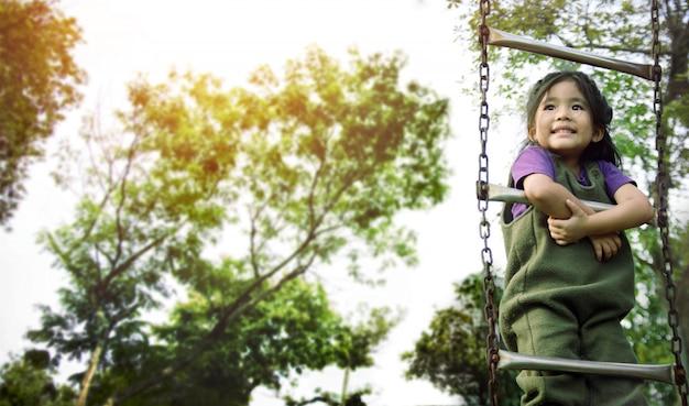 Het aziatische jonge geitje speelt trap bij openluchtplayparktuin
