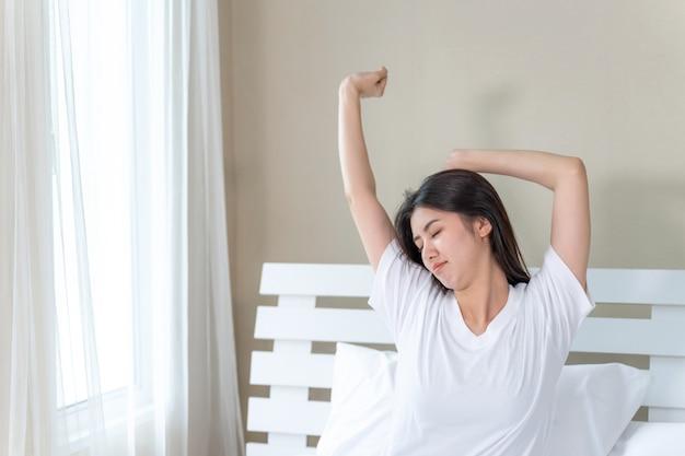 Het aziatische jonge mooie vrouw uitrekken zich in bed na kielzog omhoog in de ochtend